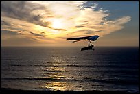 Soaring in a hang glider above the ocean at sunset,  Fort Funston. San Francisco, California, USA