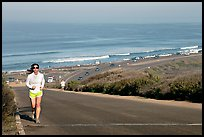 Woman jogging on raod,  Torrey Pines State Preserve. La Jolla, San Diego, California, USA