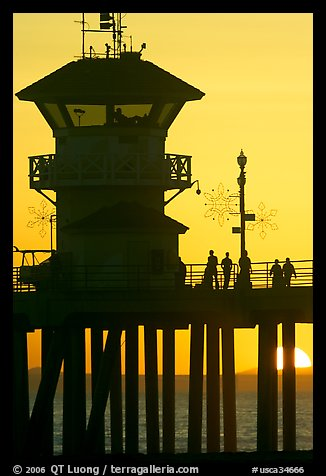 People and pier silhouetted by the setting sun. Huntington Beach, Orange County, California, USA