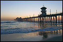 Huntington Pier reflected in wet sand at sunset. Huntington Beach, Orange County, California, USA