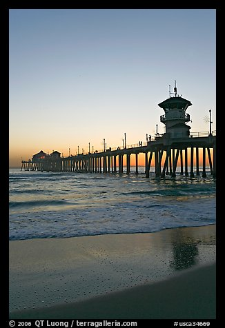 Huntington Pier and reflections in wet sand at sunset. Huntington Beach, Orange County, California, USA