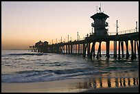 The 1853 ft Huntington Pier reflected in wet sand at sunset. Huntington Beach, Orange County, California, USA