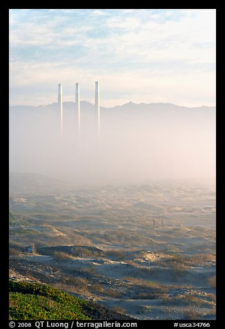 Chimneys of power plant emerging from the fog. Morro Bay, USA