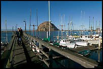 People walking on a deck in the harbor. Morro Bay, USA ( color)