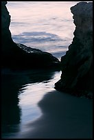 Reflection on wet sand through rock opening, Natural Bridges State Park, dusk. Santa Cruz, California, USA