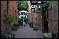 Couple walking in an alley of brick walls, San Pedro Square. San Jose, California, USA (color)