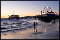 Couple on beach, with pier in the background, sunset. Santa Monica, Los Angeles, California, USA (color)