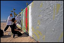 Young men creating graffiti art on a wall on the beach. Venice, Los Angeles, California, USA ( color)