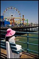 Woman sitting on bench with pink hat and ferris wheel. Santa Monica, Los Angeles, California, USA