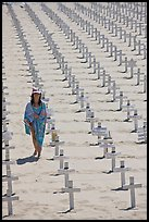 Girl wrapped in towel walking amongst crosses on beach. Santa Monica, Los Angeles, California, USA