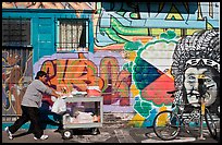Man pushes vending cart pass mural and bicycle, Mission District. San Francisco, California, USA
