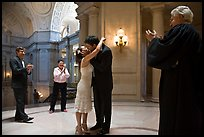Just married couple kissing, witness and officiant applauding, City Hall. San Francisco, California, USA ( color)