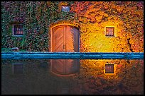 Ivy-covered facade reflected in pool at night. Napa Valley, California, USA (color)