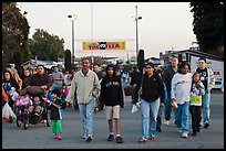 Families walking with entrance sign behind, San Jose Flee Market. San Jose, California, USA ( color)