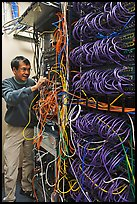 Man with tangle of wires in server room. Menlo Park,  California, USA ( color)