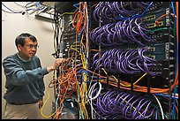 Technician rearranging data cables. Menlo Park,  California, USA ( color)