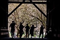 Silhouettes of dancers with sticks inside covered bridge, Felton. California, USA ( color)
