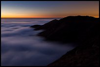 Hills emerging from sea of clouds at dusk, Garrapata State Park. Big Sur, California, USA ( color)