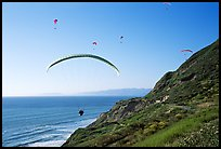 Paragliders soaring above cliffs, the Dumps, Pacifica. San Mateo County, California, USA (color)
