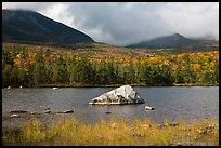 Boulder, pond, forest in autumn and mountains with clouds. Baxter State Park, Maine, USA ( color)