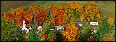 White-steppled church and houses amongst trees in fall foliage. Vermont, New England, USA (Panoramic color)