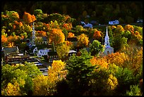 Village surounded by trees in brilliant autumn foliage. Vermont, New England, USA