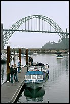 Couple holding small boat at boat lauch ramp. Newport, Oregon, USA
