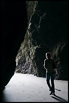 Woman walking out of sea cave. Bandon, Oregon, USA ( color)