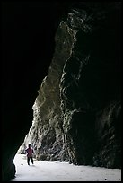 Infant walking into sea cave. Bandon, Oregon, USA (color)