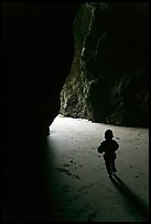 Infant walking towards the light in sea cave. Bandon, Oregon, USA (color)