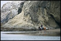 Woman horse-riding on beach next to sea cave entrance. Bandon, Oregon, USA ( color)