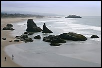 Beach at Face Rock with two people walking. Bandon, Oregon, USA