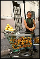 A man peels oranges to make an orange drink, which is drunk from the fruit itself, Ponce. Puerto Rico