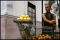 Man peeling oranges to make a drink, drunk from the fruit itself, Ponce. Puerto Rico
