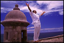 Man standing next to a lookout turret, with arms spread, El Morro Fortress. San Juan, Puerto Rico