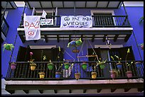 Facade of house painted in blue with pots, balconies and anti-war signs. San Juan, Puerto Rico