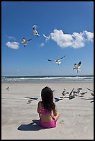 Girl sitting on beach with birds flying, Jetty Park. Cape Canaveral, Florida, USA