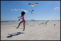 Girl jumping on beach with seagulls flying, Jetty Park. Cape Canaveral, Florida, USA