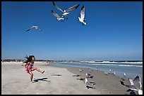 Beach with flying seagulls and girl, Jetty Park. Cape Canaveral, Florida, USA