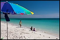 Beach with unbrella, children playing and woman strolling,. The Keys, Florida, USA