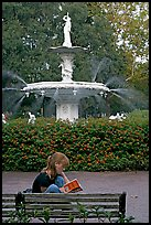 Woman sitting on bench with book in front of Forsyth Park Fountain. Savannah, Georgia, USA ( color)