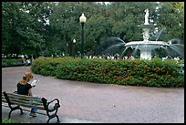 Forsyth Park Fountain with woman sitting on bench with book. Savannah, Georgia, USA ( color)