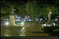 Square by night with people sitting on benches. Savannah, Georgia, USA