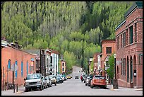 Historic brick buildings and slope with newly leafed aspens. Telluride, Colorado, USA