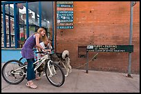 Girls on bikes and puppy parking. Telluride, Colorado, USA (color)