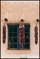 Ristras hanging from vigas and blue window. Taos, New Mexico, USA (color)