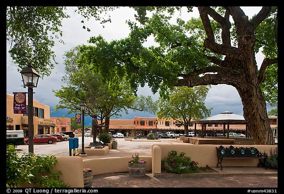 Plazza, trees and buildings in adobe style. Taos, New Mexico, USA