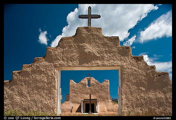 Adobe church framed by entrance in earthen wall, Picuris Pueblo. New Mexico, USA