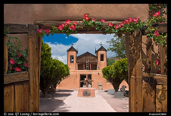 Church framed by doors with roses, Sanctuario de Chimayo. New Mexico, USA