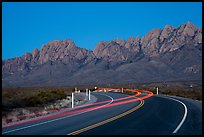 Road with light trails and Organ Mountains at dusk. Organ Mountains Desert Peaks National Monument, New Mexico, USA ( color)